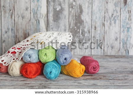 Yarns for knitting with lace on wooden background - stock photo