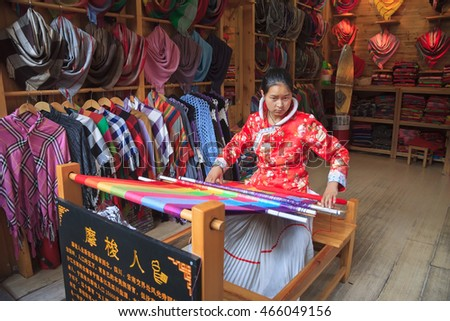 YAUNGSHUO, CHINA, SEPTEMBER 12, 2011: Chinese young woman in traditional dress weaves a scarf in a shop