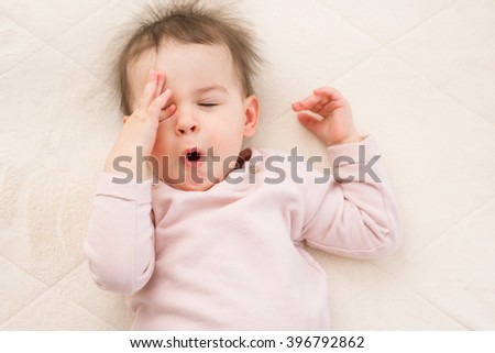 Yawning and sleeping beautiful baby toddler on the bed. Portrait - stock photo