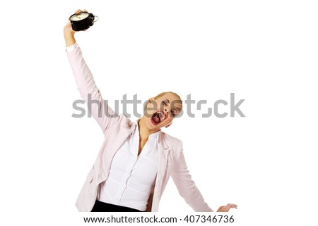 Yawning business woman holding alarm clock - stock photo