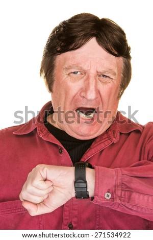 Yawning mature man looking at his watch - stock photo
