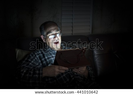 Yawning middle aged man wearing pajamas reading tablet at night in bed with copy space