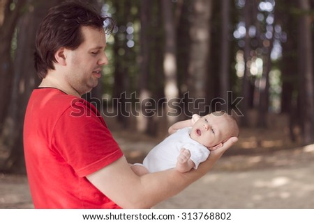 Yawning 1 month old baby lying on his father's arm during walk in the park - stock photo