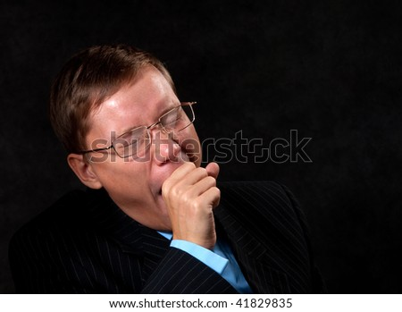 Yawning young businessman in the dark - stock photo