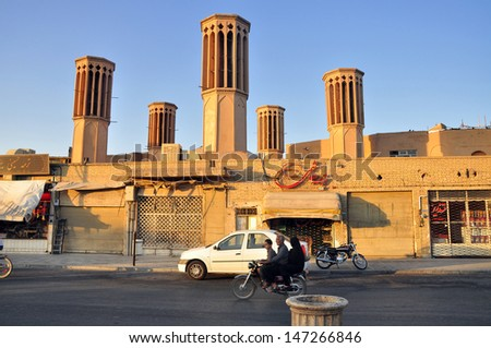 YAZD, IRAN - CIRCA AUGUST 2012: Unknown Iranian family ride by bike in front of wind towers in Yazd, Iran. Circa Aug 2012 - stock photo