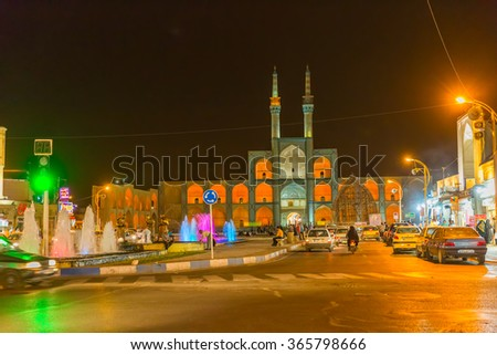 YAZD, IRAN - MAY 4, 2015: Traffic on the main intersection by the fountain in old city by night.