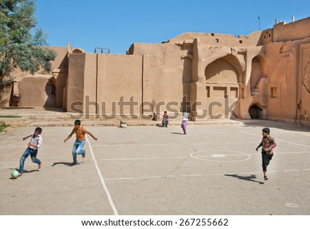 YAZD, IRAN - OCT 20: Unidentified children playing football in the street with clay houses on October 20, 2014. With population of 270.600 families, Yazd is the centre of Persian architecture - stock photo