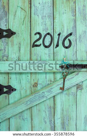 Year 2016 in black iron numbers and bronze skeleton key on antique rustic mint green wood door - stock photo