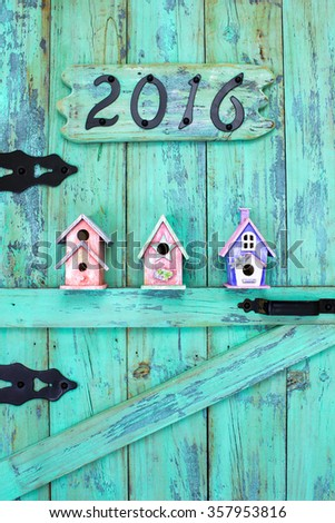 Year 2016 in black iron numbers and colorful birdhouses hanging on antique rustic teal blue wood door - stock photo
