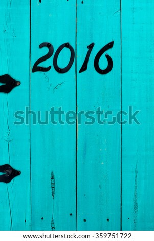 Year 2016 in black iron numbers hanging on antique rustic teal blue wooden door - stock photo