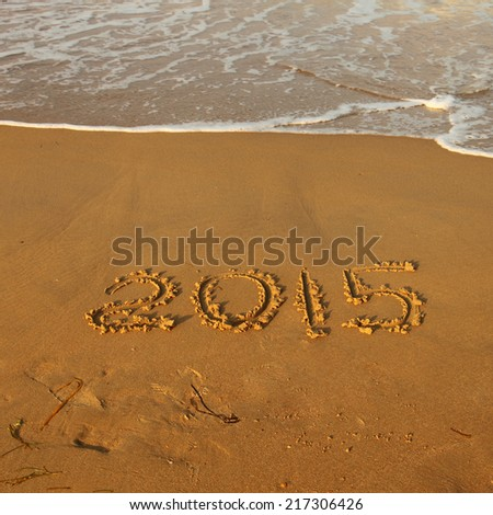 Year 2015 number written on sandy beach  - stock photo
