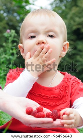 Year-old girl eating raspberries from mother's hand - stock photo