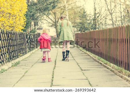 year-old girl riding her scooter on the street - stock photo
