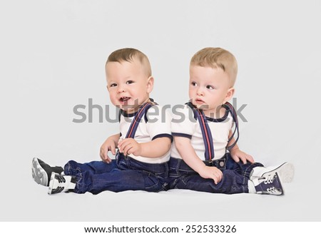 Year-old twins boys on grey backround - stock photo
