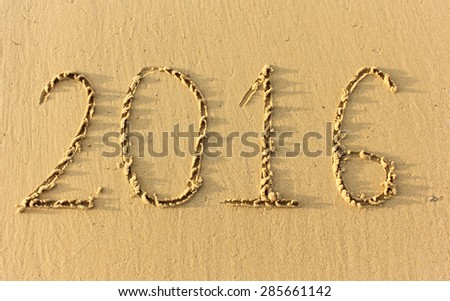 Year 2016 written in the Sand on a Beach against sunset - stock photo