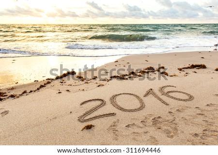 Year 2016 written on sand at sunset - stock photo