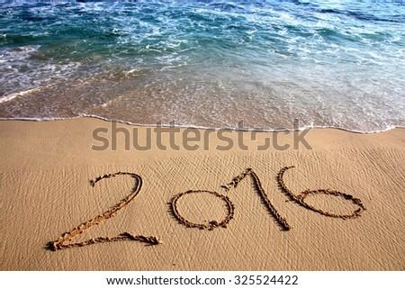 Year 2016 written on sandy beach. Symbol of the year 2016. - stock photo