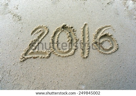 Year 2016 written on the sand at beach