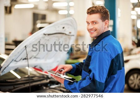 Years of mechanical experience. Confident young man working on digital tablet and smiling while standing in workshop with car in the background - stock photo