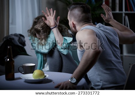 Yelling aggressive man beating his scared wife - stock photo