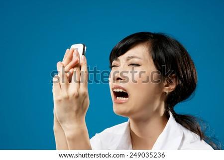 Yelling, closeup portrait of Asian business woman on studio blue background. - stock photo