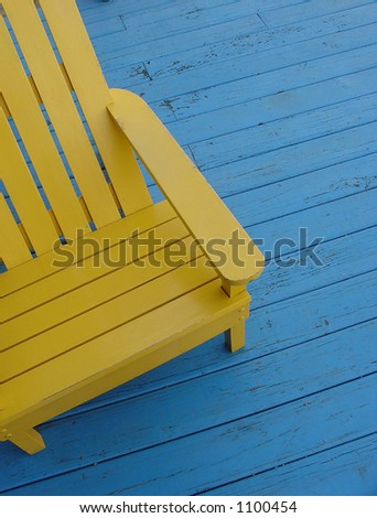Yellow adirondack chair on blue deck