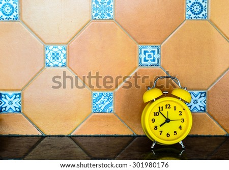Yellow alarm clock against tiled backdrop - stock photo