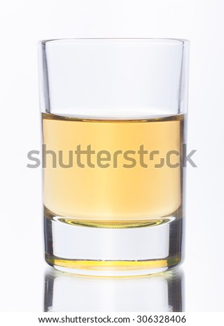 Yellow alcohol shot in transparent glass ready for drink on mirroring white background