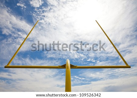 Yellow American football metal field goal against a partially cloudy sky. Viewed from below and the back of the field goal.