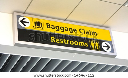 Yellow and black baggage claim and restroom sign with arrows
