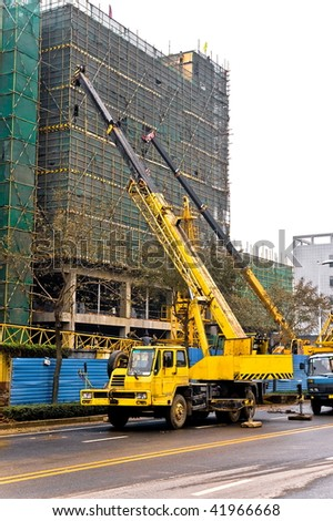 Yellow and black telescopic cranes are lifting heavy weight on construction site. - stock photo