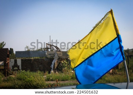 Yellow and blue flag and the ruined village at the background  - stock photo