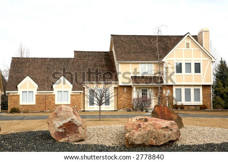 Yellow and brick modern two story home - stock photo