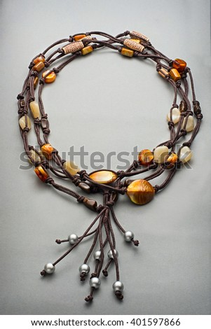 Yellow and chrome colored beads and dark leather string as bracelet over gray background - stock photo
