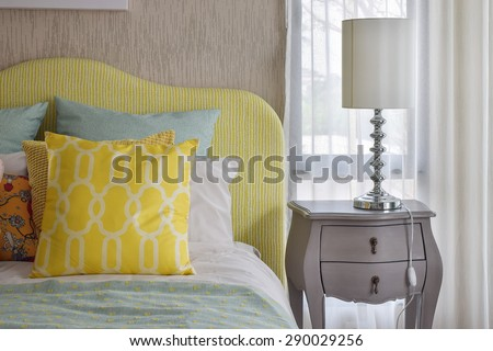 Yellow and green and pattern pillows on classic style bed and reading lamp on bedside table - stock photo