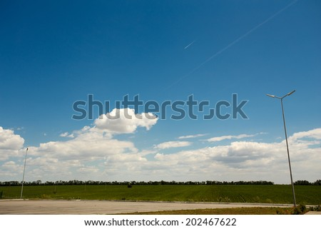 Yellow and green field and blue sky. - stock photo