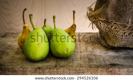 Yellow and green pears on wood table