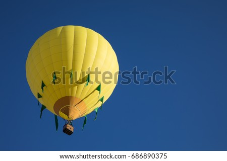 Yellow and green tear drop shaped hot air balloon with cloudless blue sky background