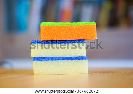 Yellow and orange cleaning sponges on wooden table - stock photo