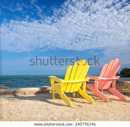 Yellow and pink colorful  lounge chairs on a beach in Florida Keys with blue sky on a sunny summer day - stock photo