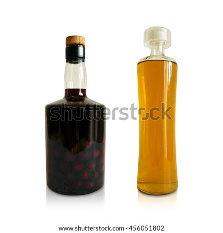Yellow and red brandy bottles. Vintage liquor alcohol beverages isolated on clear white background. Alcoholic, bourbon, liquor cherry and plum drinks. - stock photo