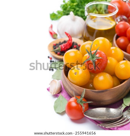 yellow and red cherry tomatoes in wooden bowl, olive oil and spices, isolated on white - stock photo