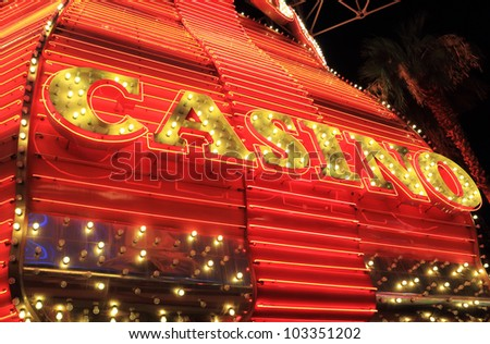 Yellow and red neon lights surround casino sign - stock photo