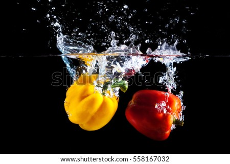 Yellow and red sweet pepper splash into a black color of water