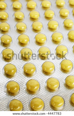 Yellow and round tablets in a factory packing - stock photo