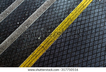 Yellow and white stripped anti-slip pedestrian steps with diagonal patterns providing safety and protection for workers - stock photo
