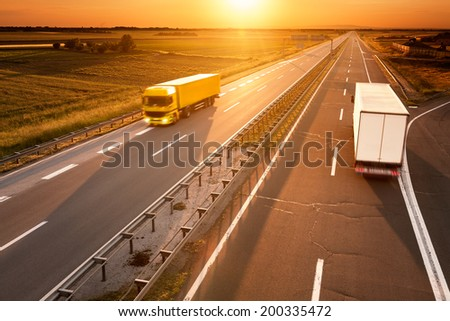 Yellow and white truck in motion blur on the highway at sunset - stock photo