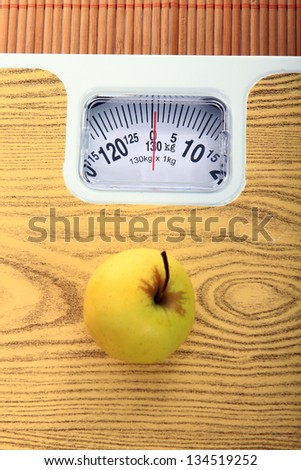 yellow apple and measure tape above the balance - stock photo