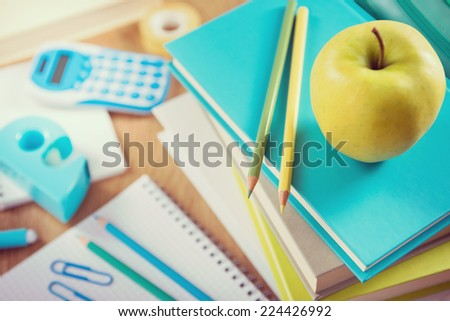 Yellow apple on a pile of books with colorful stationery, back to school concept. - stock photo