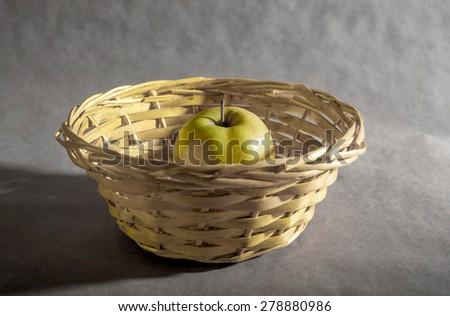 yellow apple on yellow basket - stock photo